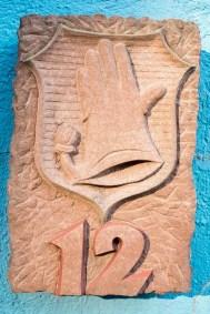 Stein mit Handschuh-Wappen und der Hausnummer 12.