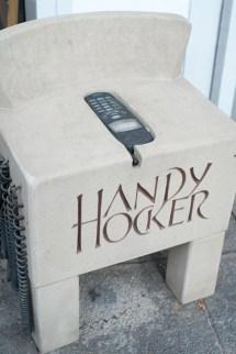 """Ein grauer kleiner Hocker mit der Aufschrift """"Handy Hocker"""". Eingelassen ist ein Mobiltelefon aus den Neunzigern."""