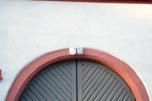 Oberteil eines großen Tors, darüber zwei kleine Wappen eines mit Handschuh