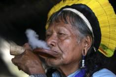 Brazilian Indian Chief Raoni smokes a pipe before a protest at the Esplanada dos Ministerios in Brasilia