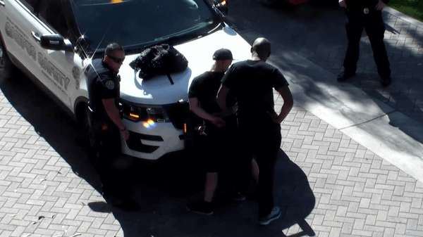 Two officers arrest a man on a campus safety vehicle