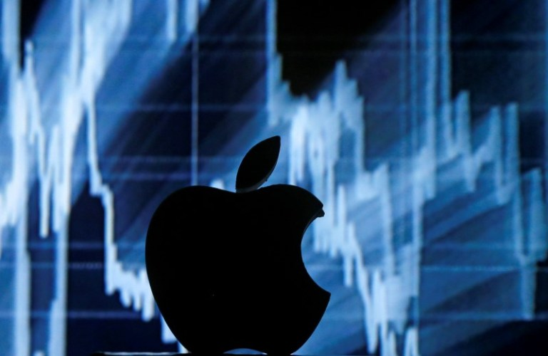 A 3D printed Apple logo is seen in front of a displayed stock graph in this illustration taken