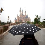 A woman holds a Mickey Mouse umbrella as she visits Shanghai Disney Resort during a three-day Grand Opening events in Shanghai