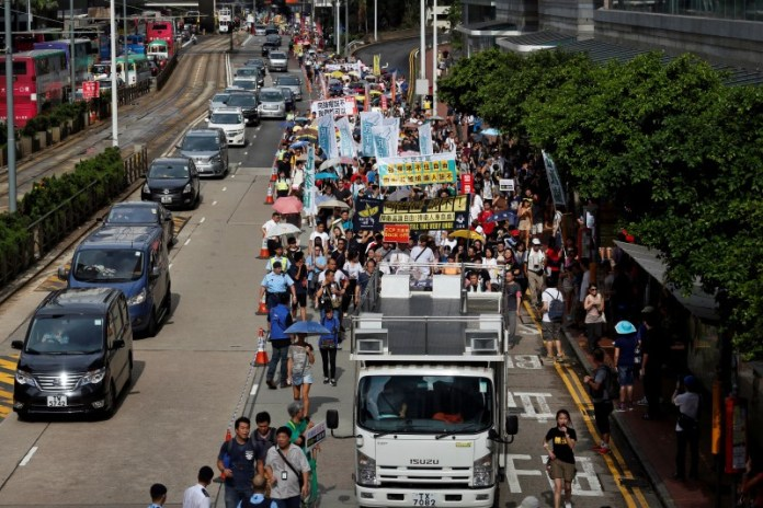 Supporters of bookseller Lam Wing-kee, who returned from mainland China after being detained, take part in a protest march in Hong Kong, China June 18, 2016.      REUTERS/Bobby Yip