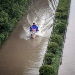 A rider drives past a flooded street in Changzhou, Jiangsu Province.   REUTERS/Stringer