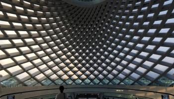 A woman stands on an escalator at Yujiapu high speed railway station in Tianjin