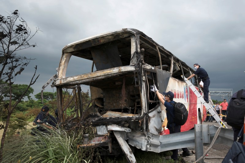 Police and other emergency personnel work around the wreckage of a bus that crashed en route to Taoyuan airport, just south of the capital Taipei July 19, 2016.  REUTERS/A-Kun Li