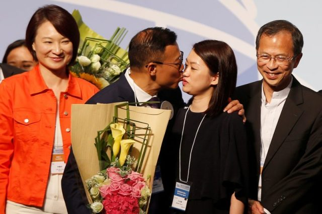 Horace Cheung Kwok-kwan kisses his wife beside Starry Lee (L), chairman of the Democratic Alliance for the Betterment and Progress of Hong Kong, and former Chairman of the Legislative Council Jasper Tsang, after Cheung won a seat at the Legislative Council election in Hong Kong, China September 5, 2016. REUTERS/Bobby Yip