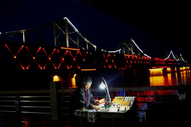 A woman sells cigarettes in front of the bridge across Yalu River that connects China's Dandong, Liaoning province, and North Korea's Sinuiju September 10, 2016. REUTERS/Thomas Peter
