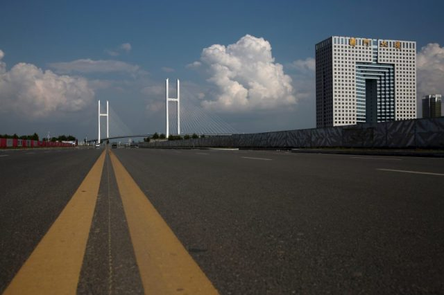 An empty street runs in front of the unfinished New Yalu River bridge (L) and the empty Chinese customs building in Dandong, Liaoning province, China, September 11, 2016. The bridge was designed connect China's Dandong New Zone and North Korea's Sinuiju. REUTERS/Thomas Peter
