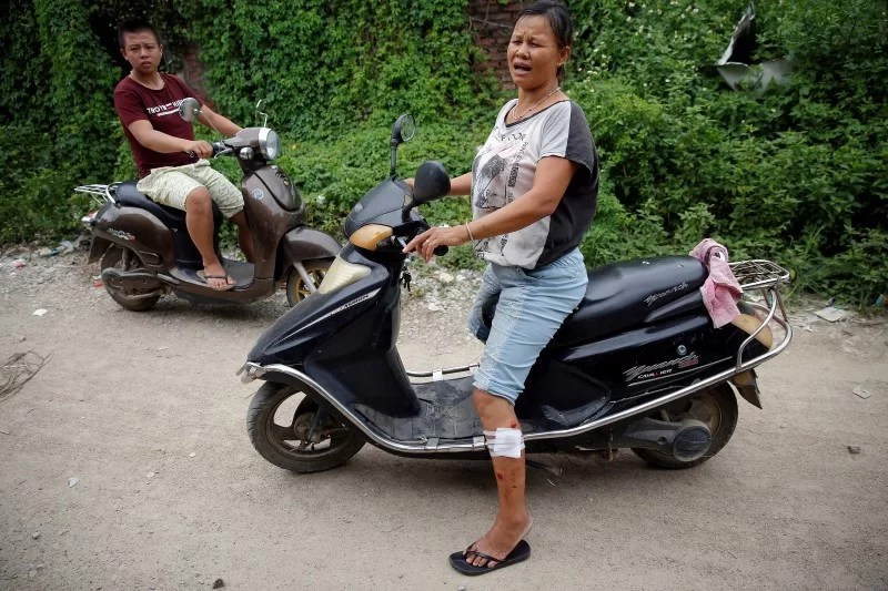 A woman who claimed injured during the violence on Tuesday rides a scooter in Wukan