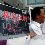 "Protesters demonstrate with a placard which reads ""Support Wukan village"" outside China Liaison Office in Hong Kong"