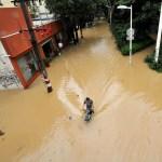 A man rides through a flooded street after Typhoon Meranti made landfall on southeastern China, in Fuzhou