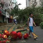 People walk past uprooted trees after Typhoon Meranti made a landfall on southeastern China, in Xiamen