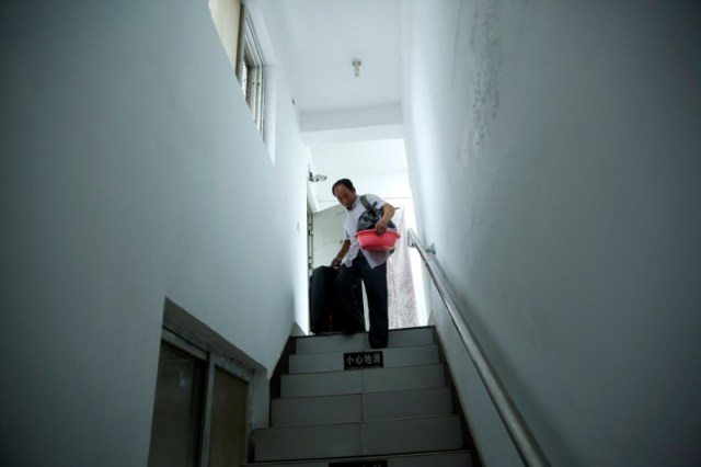 Pan carries his belongings as he prepares to check out of the accommodation where some patients and their family members stay while seeking medical treatment in Beijing, China, June 23, 2016. REUTERS/Kim Kyung-Hoon