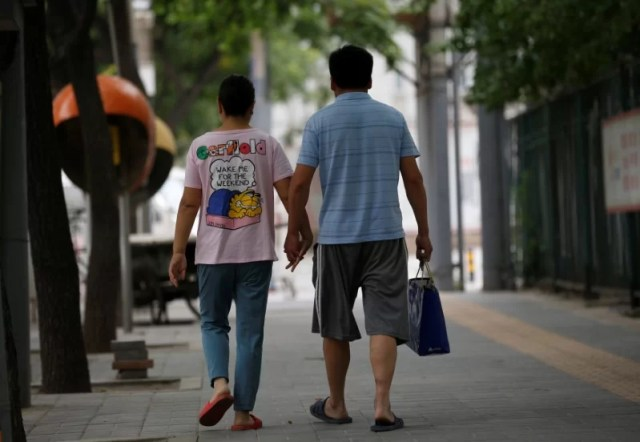 Wang and her husband Liu hold hands as they walk toward a hospital in Beijing, China, June 23, 2016. REUTERS/Kim Kyung-Hoon
