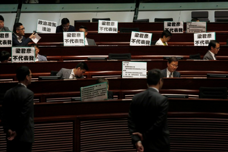 """Pro-democracy protesters display placards which read """"Andrew Leung does not represent me"""", referring to the Legislative Council president, during a demonstration inside the council's chamber in Hong Kong, China October 26, 2016.  REUTERS/Bobby Yip"""