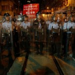 Riot police stand on a tram track during a standoff with protesters outside China Liaison Office in Hong Kong