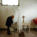 Bishop Emeritus of Luoyang Pei Ronggui waits to take confession from members of the congregation before Sunday service at an unofficial catholic church in Youtong village