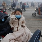 People wear face masks as heavy smog blankets Shenfang in Hebei province, on an very polluted day