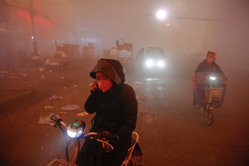 People make their way through heavy smog on an extremely polluted day with red alert issued, in Shengfang