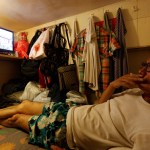 """Unemployed Hong Kong resident Simon Wong, 61, watches TV inside his 4-by-6-feet partitioned unit, or """"coffin unit"""", with a monthly rent of HK$1,750 ($226) in Hong Kong"""