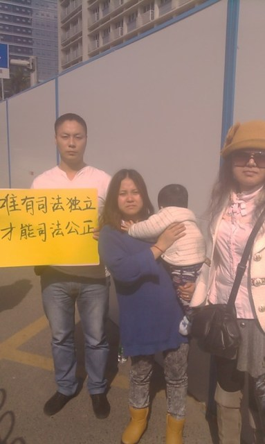 Wang Dengchao's wife and child (middle) and supporters outside the court.