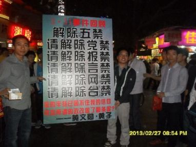 Two Guangdong activists holding a sign demanding freedoms.