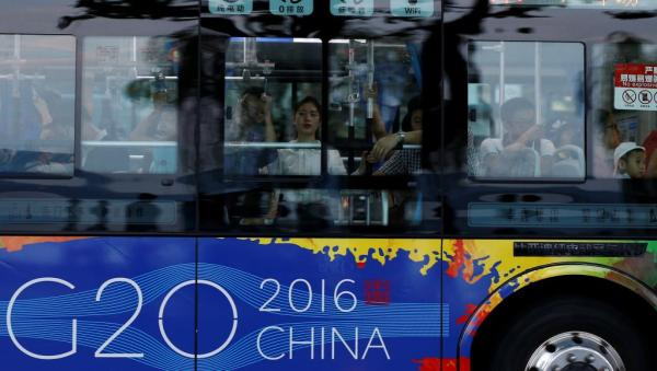 杭州G20峰会即将召开,驶过西湖旁的公交车也贴着G20招贴。