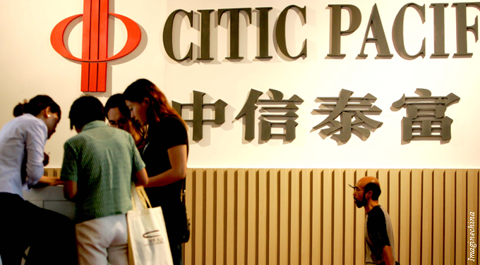 people walk past citic pacific logo