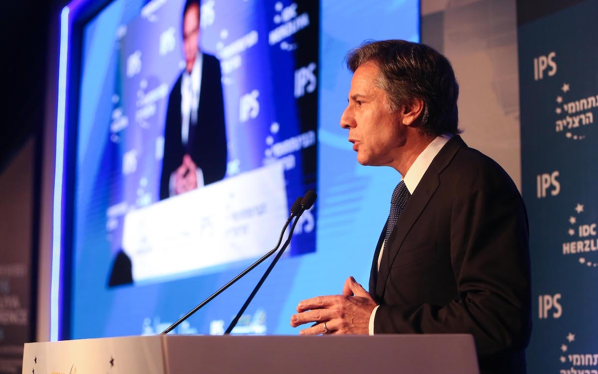 The photo shows US Secretary of State Antony Blinken talking from a podium with his image flashed up on a large television screen. He has sent a warning to China about its behaviour on the global stage.