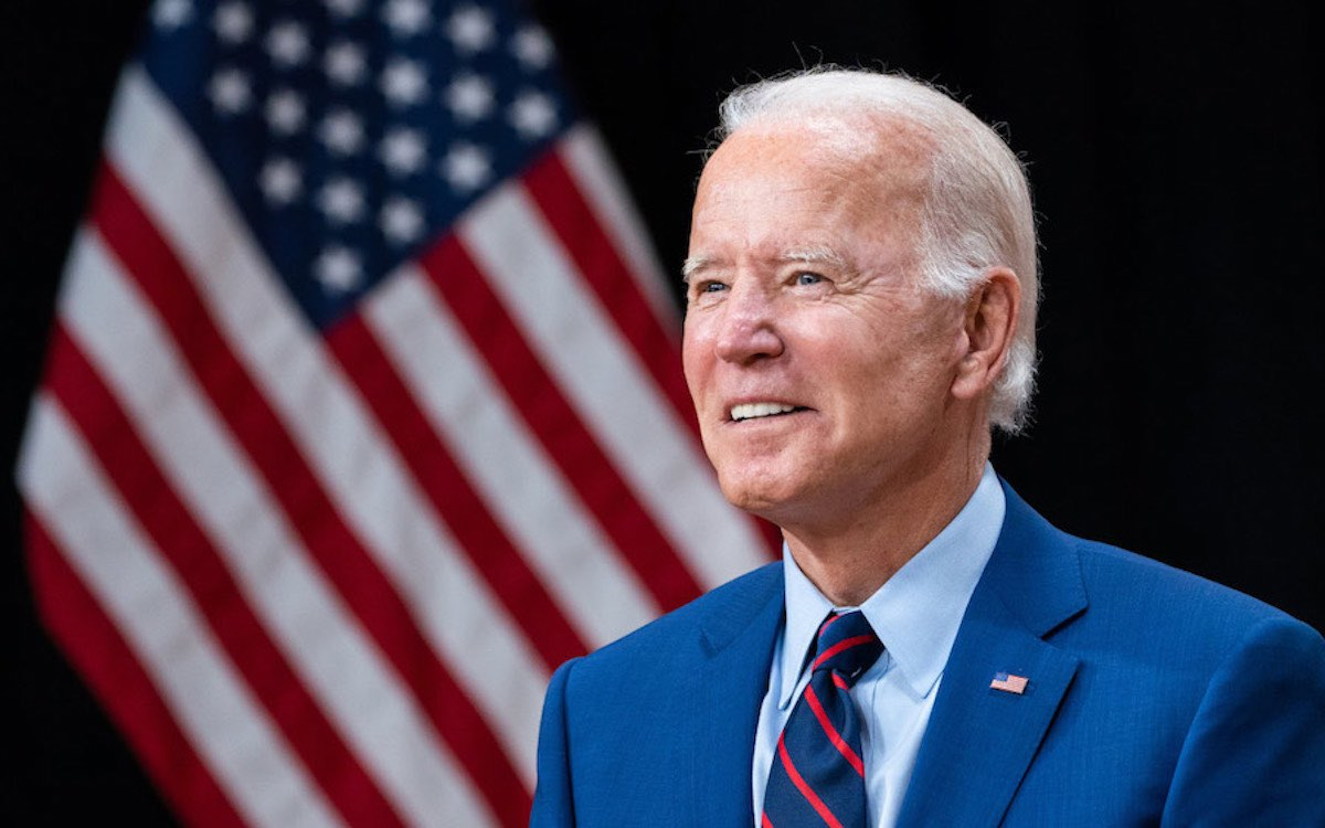 The photo shows Joe Biden in a blue suit standing in front of a US flag. He has issued a veiled warning to China.