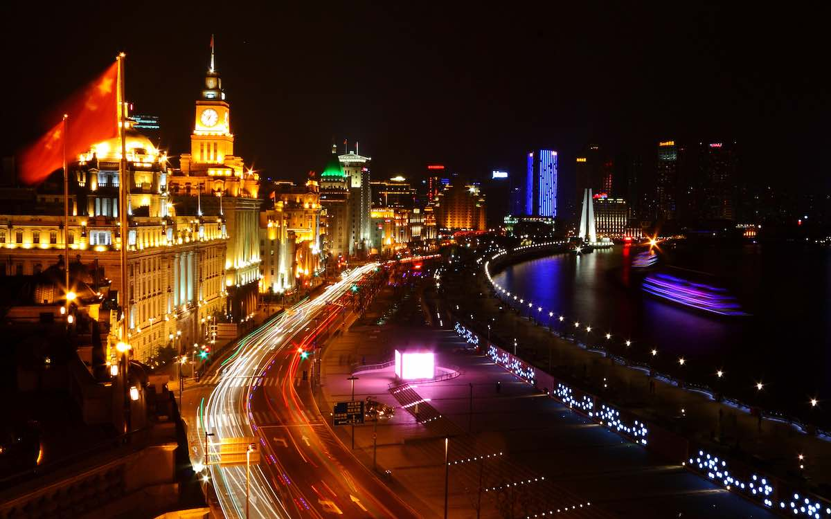 The image shows a speed frame of Shanghai at night, highlighting a kaleidoscope of colors. The New Silk Road has the potential to change the world.