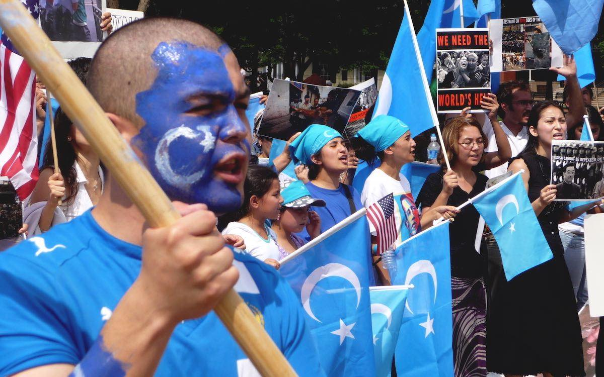 The image shows a sea of blue during anti-China protests against Uyghur repression.