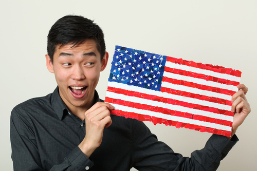 Young Asian student showing US national flag and looking sideways