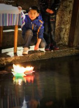 A chinese boy lights a candle for chinese new year.