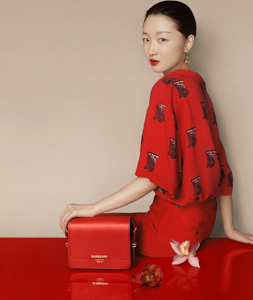 Models Zhou Dongyu, Liang Jiyuan, and He Cong are featured in Burberry's 2020 Chinese New Year campaign in bright red accessories and fashion. Designer: Ricardo Tisci. Photography by Leslie Zhang. Image via Burberry