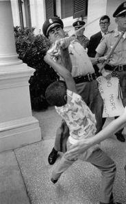 Anthony Quin, fils d'Aylene Quin, malmené par un policier refusant de lui rendre un drapeau américain accompagné d'un message contre la brutalité policière à l'encontre des défenseurs des droits civiques. Le petit garçon avait accompagné sa mère, arrêtée pour avoir réclamé une audience avec Paul Johnson, gouverneur du Mississippi, afin de protester contre les membres du congrès s'opposant au droit de vote des personnes de couleur. Jackson (Mississippi, Etats-Unis), 17 juin 1965. Photographie de Matt Herron qui a reçu le 2ème prix du World Press 1965.