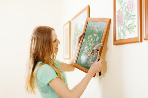 Smiling blonde woman hanging  picture