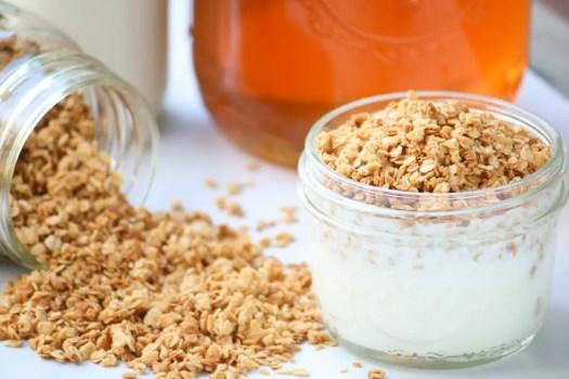 frasco de vidrio con yogurt y granola encima