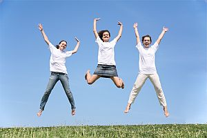 Three girlfriends in white T-shorts jump having waved hands