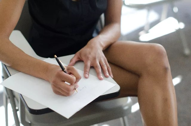 椅子に座って脚を組んで仕事をしている女性