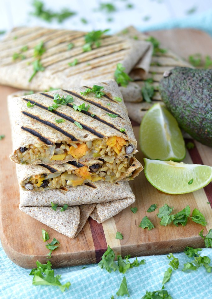vegetarian burritos stacked on each other on cutting board