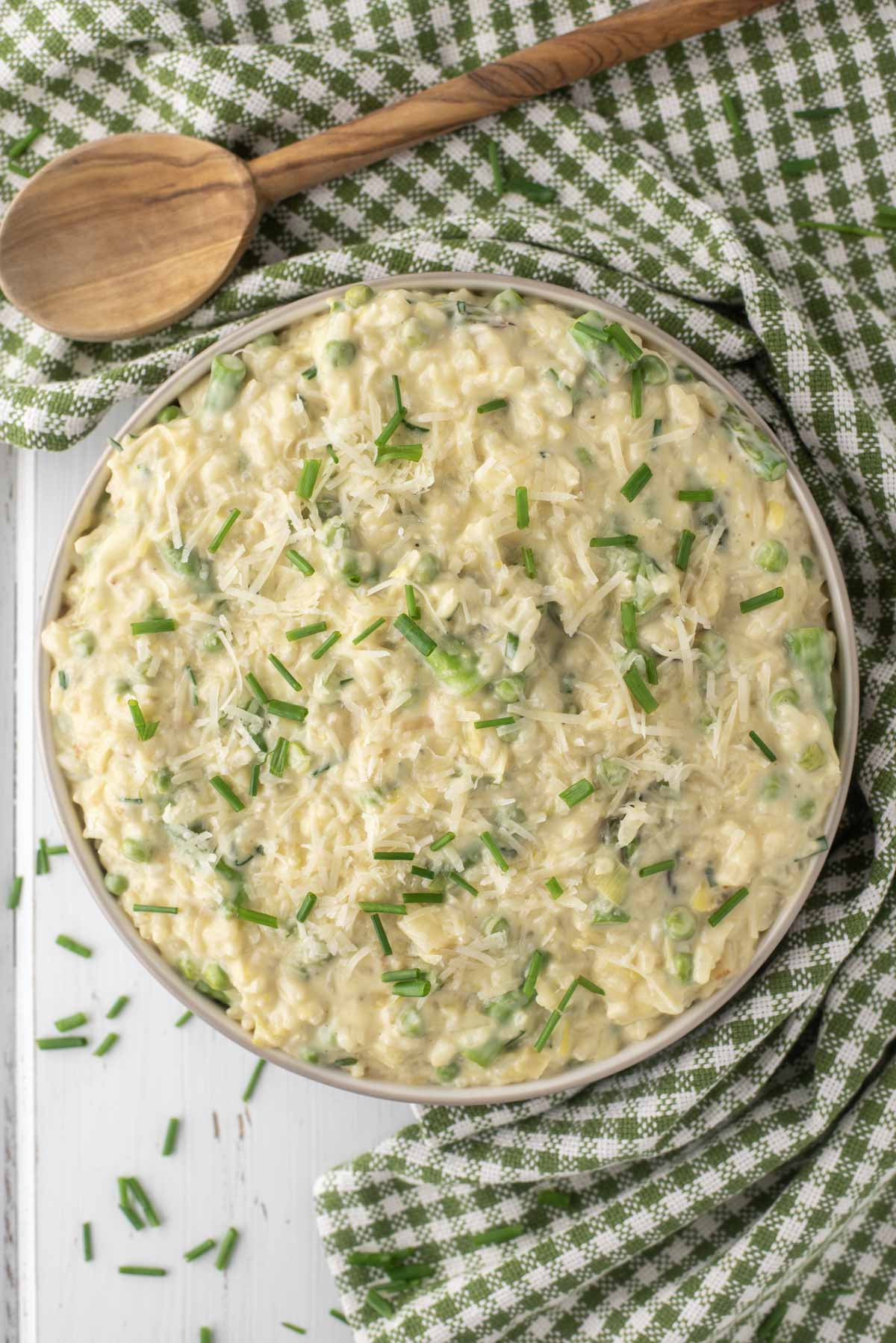 overhead shot of spring risotto in bowl with dish towel