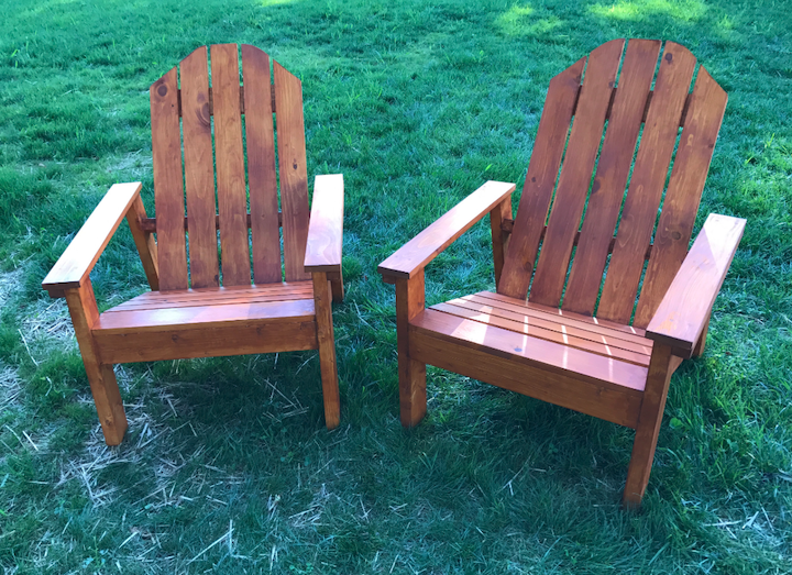 two homemade Adirondack chairs that are stained built from plans