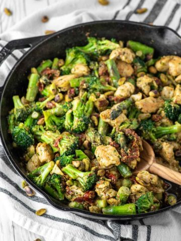 one pan pesto chicken and veggies in cast iron skillet with wooden spoon dipped in