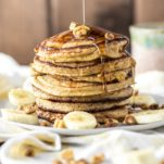 banana oat pancakes stacked on plate with maple syrup being drizzled on top