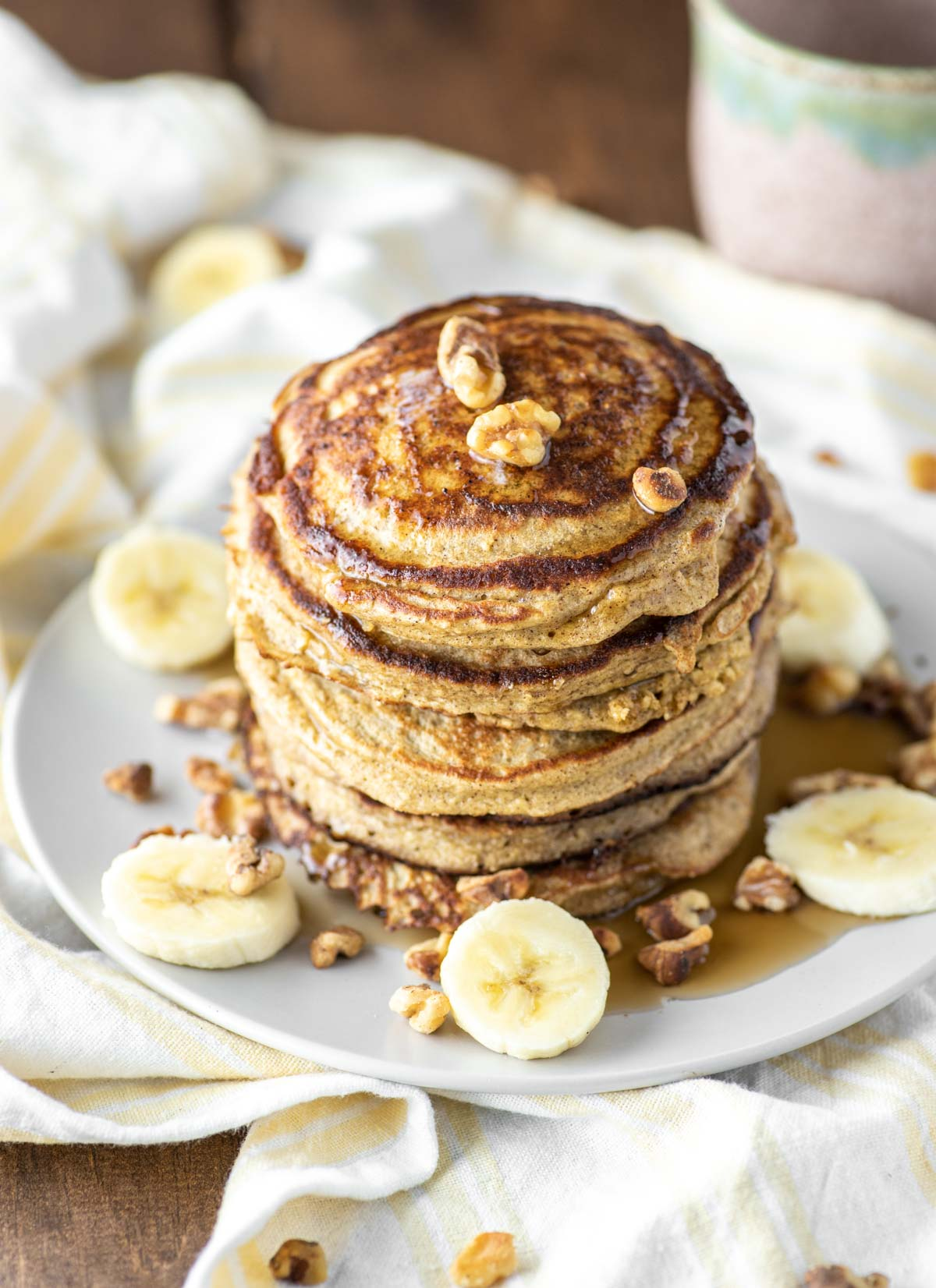 overlay of two white plates of banana pancakes with oats