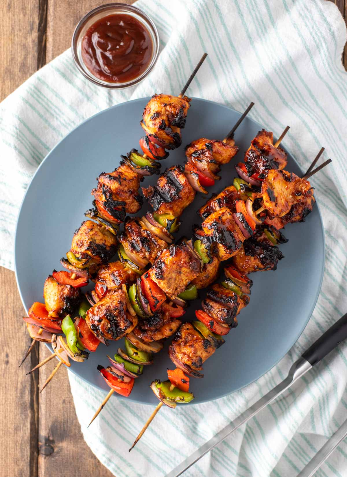 overhead shot of BBQ chicken kebabs on grey blue plate