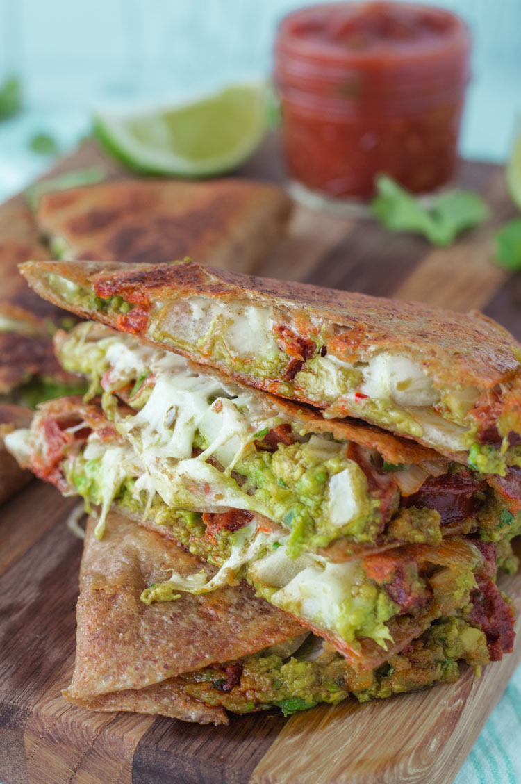 close-up of stacked chorizo and avocado quesadillas on cutting board